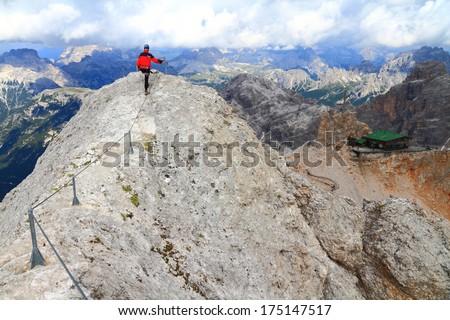 "Climber descending towards refuge on via ferrata ""Ivano Dibona"", Dolomite Alps, Italy - stock photo"