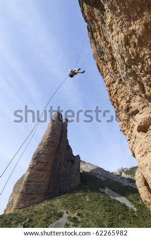 climber descending with the technique of rappelling in Riglos mountains - stock photo