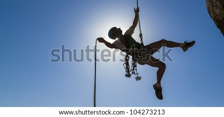 Climber free rappells from the summit after a challenging ascent. - stock photo