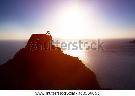 Climber giving hand and helping his friend to reach the top of the mountain. Help, support, assistance, teamwork in a dangerous situation concepts - stock photo