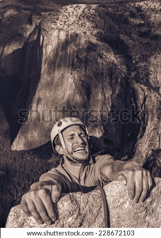 Climber holding onto the edge of an abyss for the skin of his teeth. - stock photo