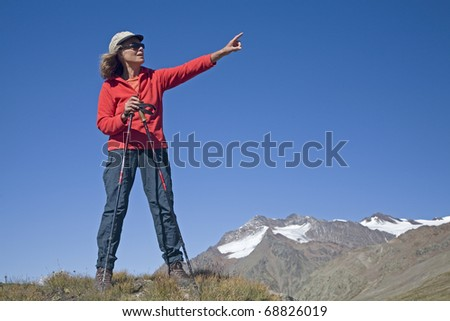 Climber in the mountains - shows the viewer  the summit - stock photo
