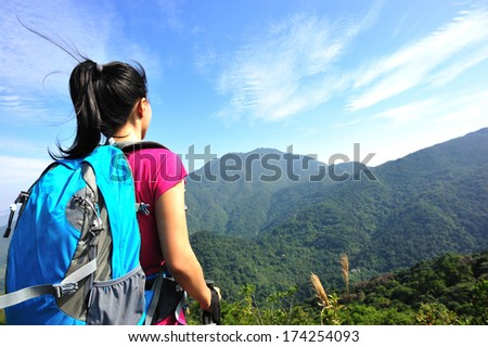climber looking into the wilderness on mountain peak  - stock photo