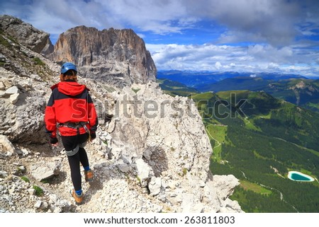 "Climber of via ferrata ""Meisules"" on sunny cliffs of Sella massif, Dolomite Alps, Italy - stock photo"