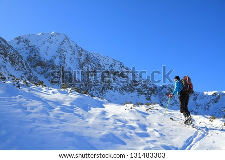 Climber on skies ascending a snow covered mountain slope - stock photo
