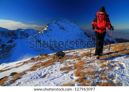 Climber on the mountain at sunset, during winter, Retezat mountains, Romania - stock photo
