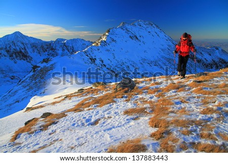 Climber on the mountain at sunset, during winter, Romania - stock photo