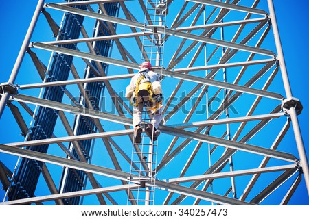 Climber on the self support cell tower - stock photo