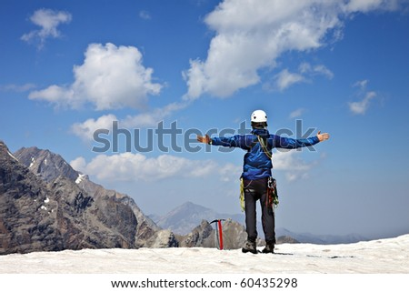 Climber on the top of the snowy mountain enjoy sunny day - stock photo