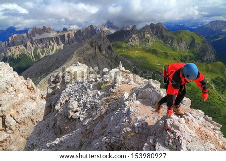 Climber on top of Averau peak after finishing via ferrata route, Dolomite Alps, Italy - stock photo