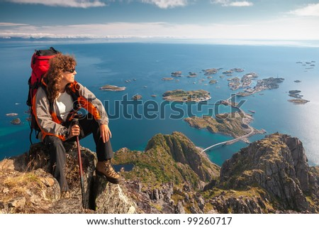 climber on top of rock near ocean - stock photo