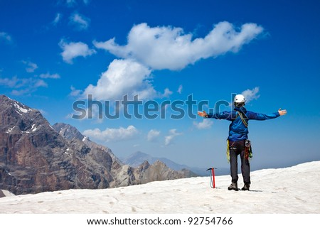 Climber on top of snow summit - stock photo