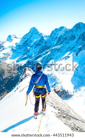 Climber reaches the summit of mountain peak. Climbing and mountaineering sport concept, Nepal Himalayas - stock photo