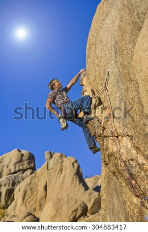 Climber struggles to grip the  summit of a challenging cliff. - stock photo