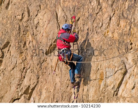 climber swarming up the rock - stock photo