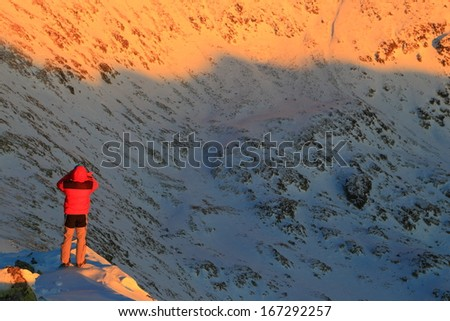 Climber taking pictures of snowy mountains at sunset - stock photo