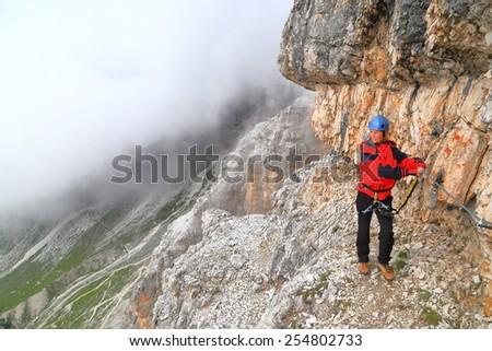 """Climber walking along steep mountain side on via ferrata """"Punta Ana"""", Tofana massif, Dolomite Alps, Italy - stock photo"""