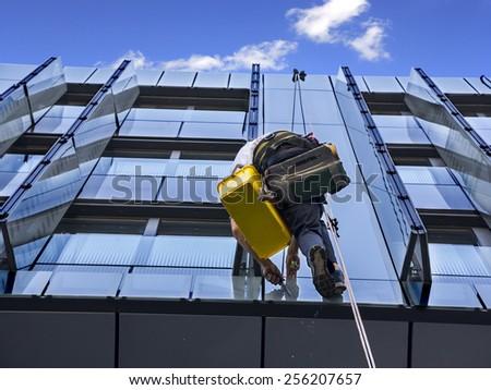 Climber wash windows and glass facade of the skyscraper  - stock photo