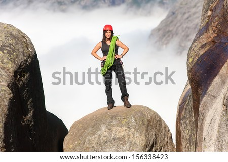 climber with a rope on the rock top - stock photo