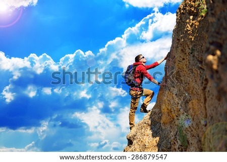 climber with backpack hanging on the rock - stock photo