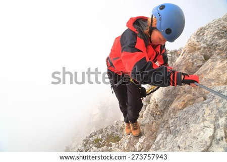 "Climber woman holding on the steel cable of via ferrata ""Punta Ana"", Tofana massif, Dolomite Alps, Ital - stock photo"