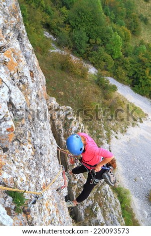 Climber woman managing rope and gear on vertical rock wall  - stock photo