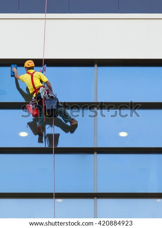 Climber worker washing windows of the modern building. - stock photo