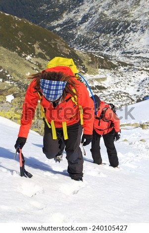 Climbers ascending a steep snow covered mountain in sunny winter day - stock photo