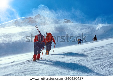 climbers at the top of a pass with backpacks meeting the sunrise in the mountains - stock photo