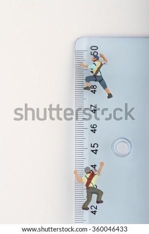 climbers miniatures on a ruler - stock photo