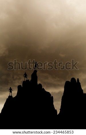 Climbers on the summit of a challenging cliff. - stock photo