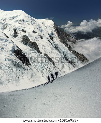 Climbers silhouette in massif de mont Blanc on the border of France and Italy ( alps). - stock photo