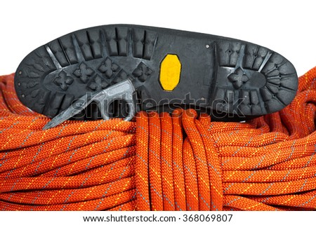 Climbing Equipment on White Background / Rock climbing equipment with a sole of mountaineering boot, old climbing piton and red rope. Isolated on white background - stock photo