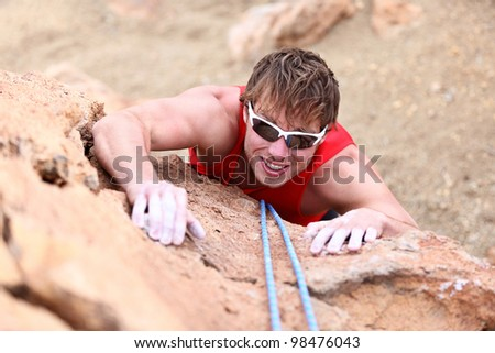 Climbing. Male climber rock climbing cliff wall with climb rope. Strong man climber on the way to summit at success. - stock photo