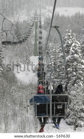 Climbing mountain in a skilift - stock photo