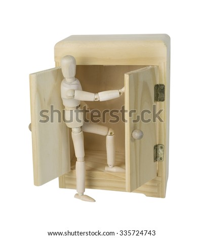 Climbing out of a Wooden wardrobe used to hold clothing in lieu of a closet - path included - stock photo