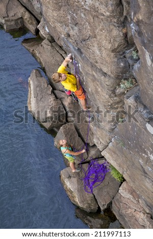 Climbing partners make ascent on to the rock wall. Two climbers - male and female - climb rocky wall over the river rocky beach. Young male climber is leading, female teenager is belaying him. - stock photo
