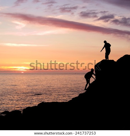 Climbing silhouette at rocky seashore gets a helping hand to get up during sunset in Brittany, France - stock photo