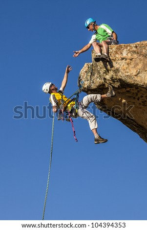 Climbing team struggle to the summit of a challenging rock mountain. - stock photo