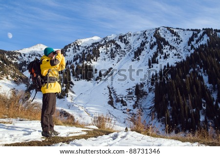 Climbing young adult looking through binoculars. Aerial view of mountain and blue sky - stock photo