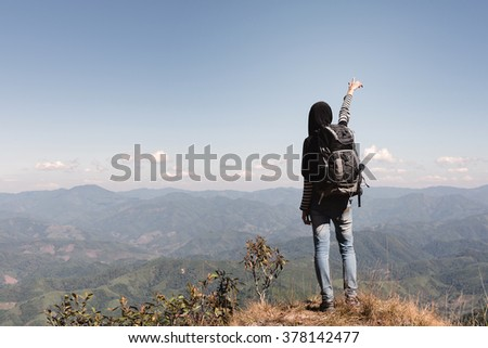 Climbing young muslim woman adult at the top of summit with aerial view of mountain range, woman is pointing straight - stock photo