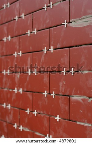 Clinker tiles arranging to wall with pegs. - stock photo