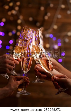 Clinking glasses of champagne in hands on bright lights background - stock photo