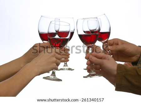 Clinking glasses of red wine in hands isolated on white - stock photo