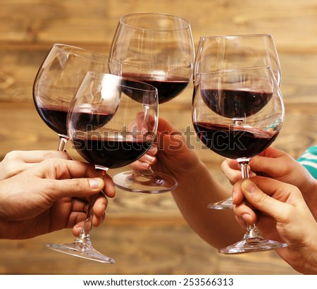 Clinking glasses of red wine in hands on rustic wooden planks background - stock photo