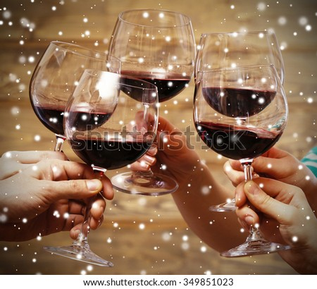 Clinking glasses of red wine in hands on wooden background over snow effect - stock photo