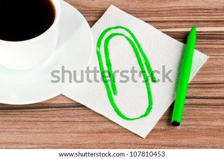 Clip on a napkin and cup of coffee - stock photo