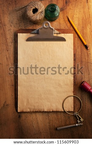 Clipboard and blank paper under incandescent light, with vintage feeling. - stock photo