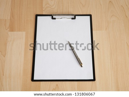 Clipboard with blank paper and a pen on the table - stock photo
