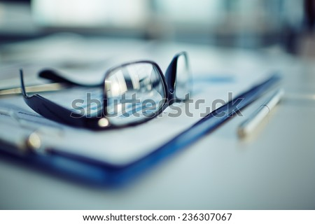 Clipboard with document, pen and eyeglasses - stock photo